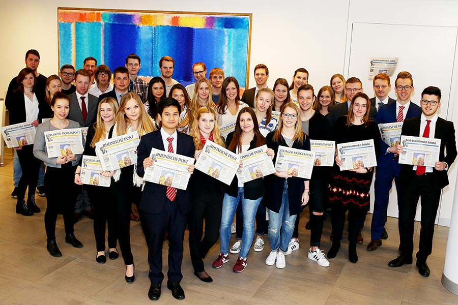 Gruppe von Menschen die eine Zeitung der Rheinischen Post in der Hand hält