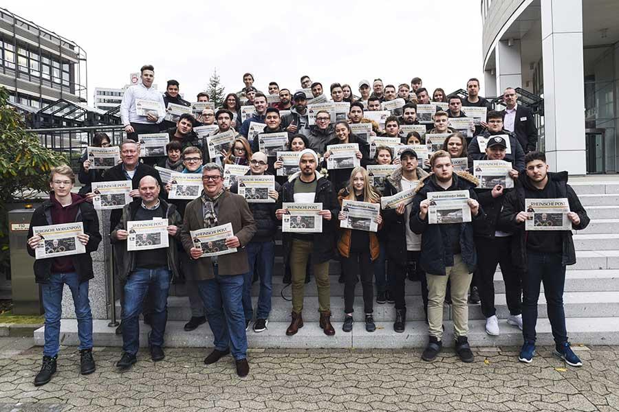 Gruppe von Menschen auf grosser Treppe mit RP Zeitung in der Hand