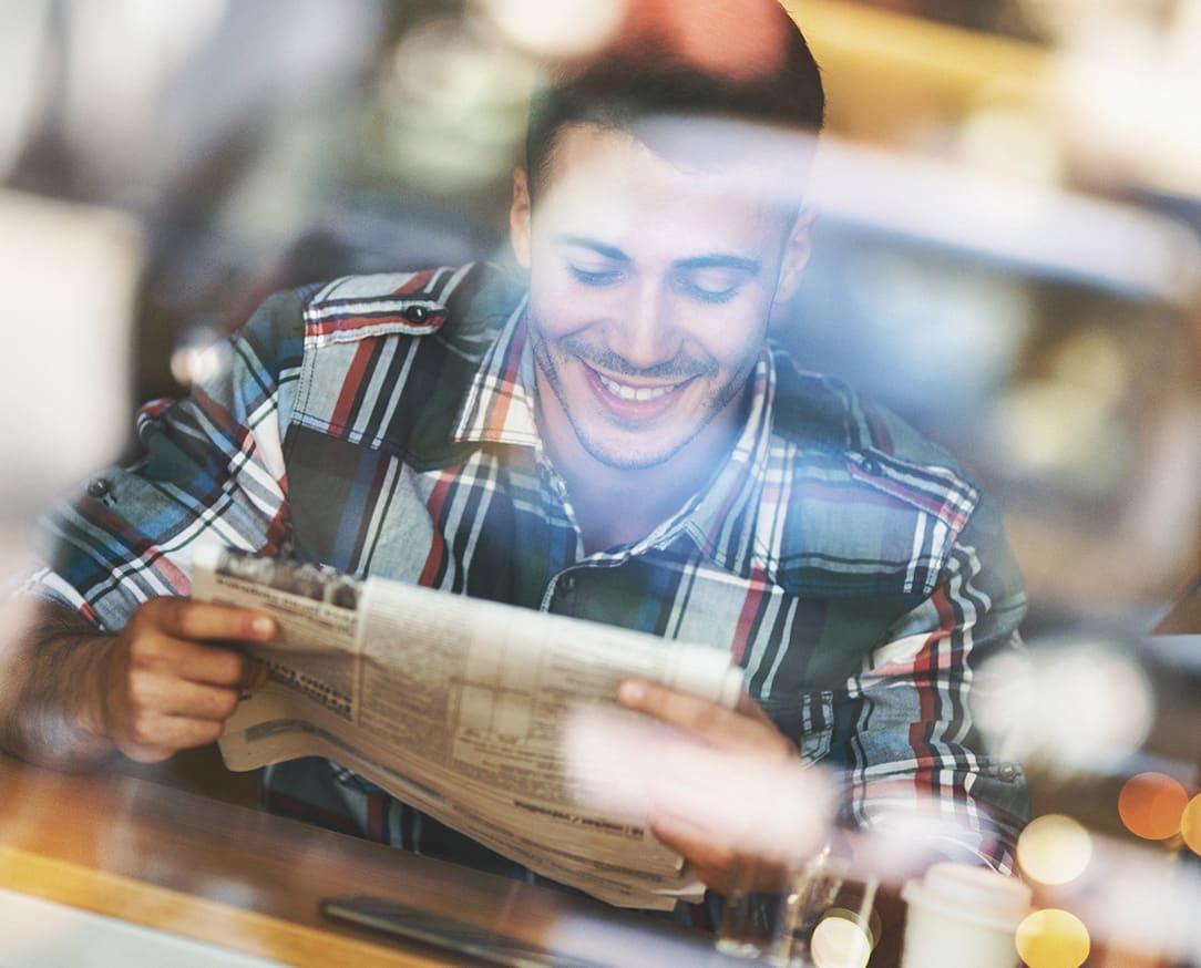 Junger Mann sitzt am Tisch und liest lächelnd eine Zeitung