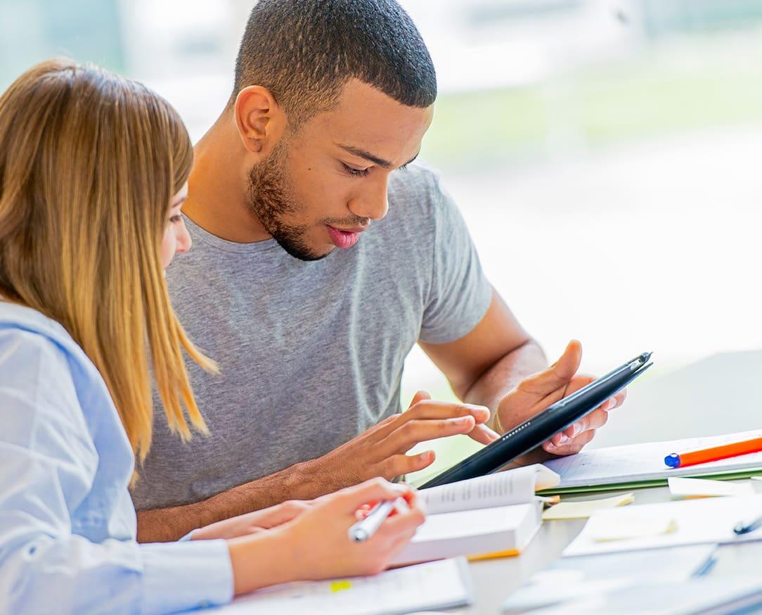 Mann und Frau am Tisch mit offenen Büchern und einem Tablet