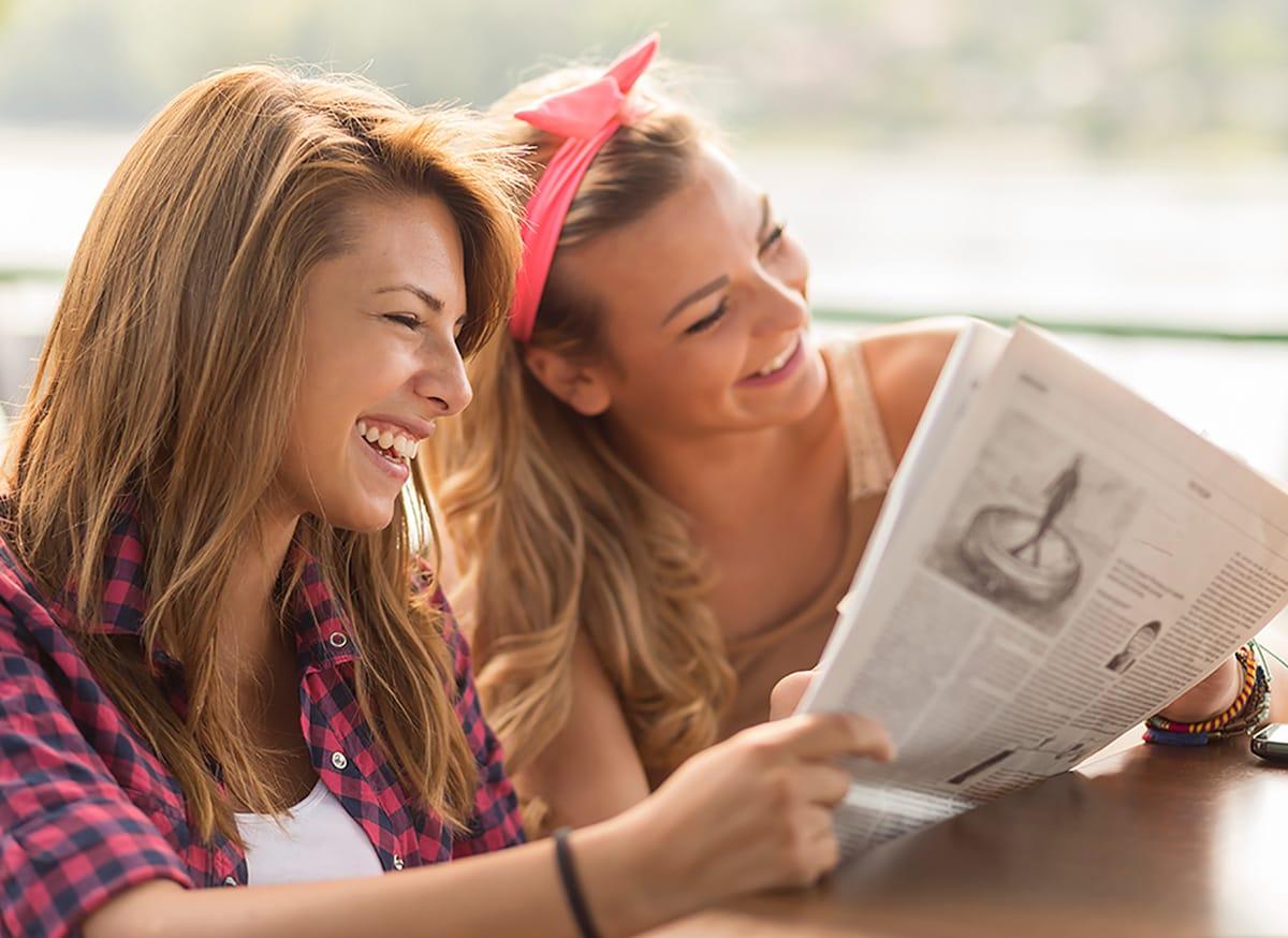 Zwei junge Frauen lesen gemeinsam Zeitung